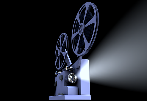 Here Are The Best Home Theater Systems For 2020-2021. In this picture, a projector sat atop a table as part of a home theater system is shown.