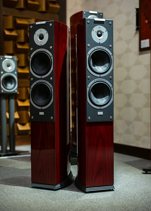 Two cherry wood tower speakers are shown.