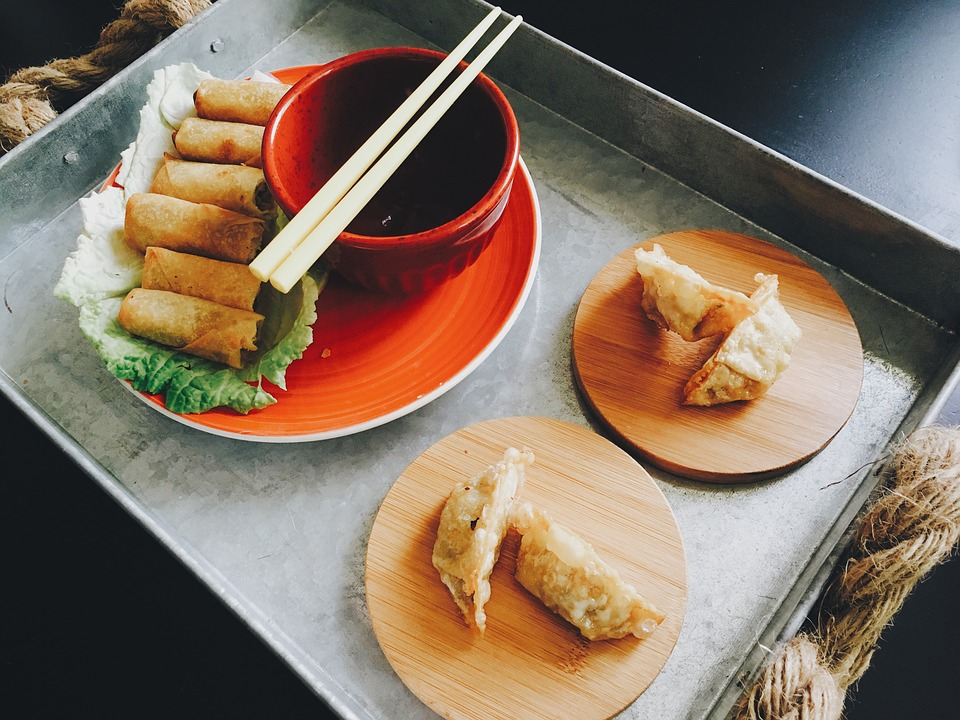 A picture of potstickers and egg rolls are shown