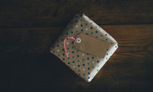 A speaker that is wrapped in star patterned wrapping paper. This is one of many possible home theater gift ideas.