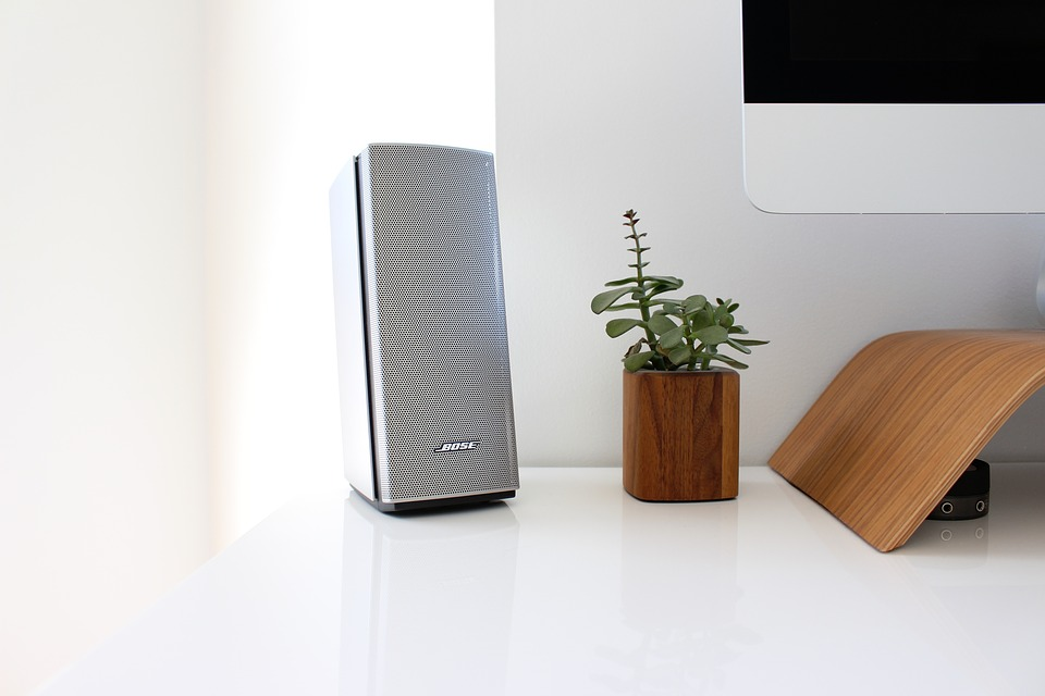 A picture of a small white surround sound speaker