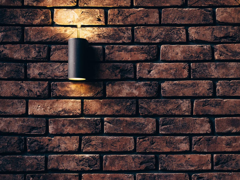 A picture of a subtle downlighting cast over a brick wall