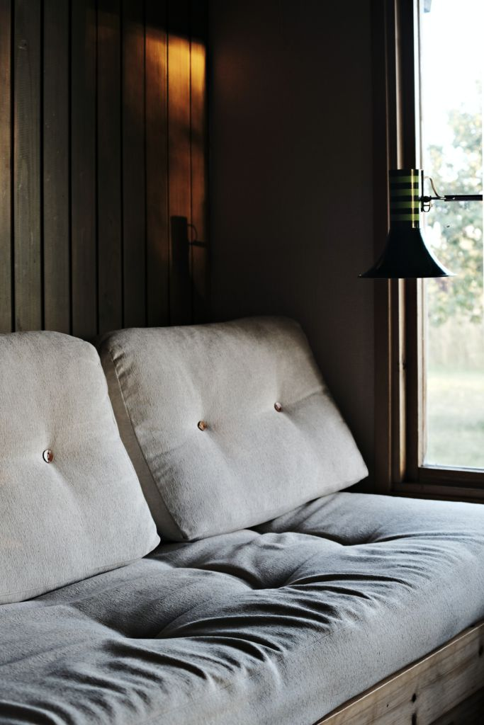A picture of a couch with slight lighting emanating from a window