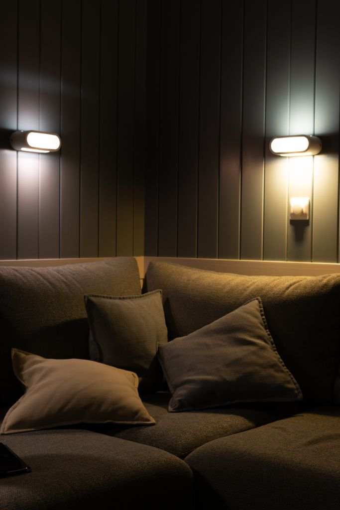 A couch with ambient lighting radiating from the wall