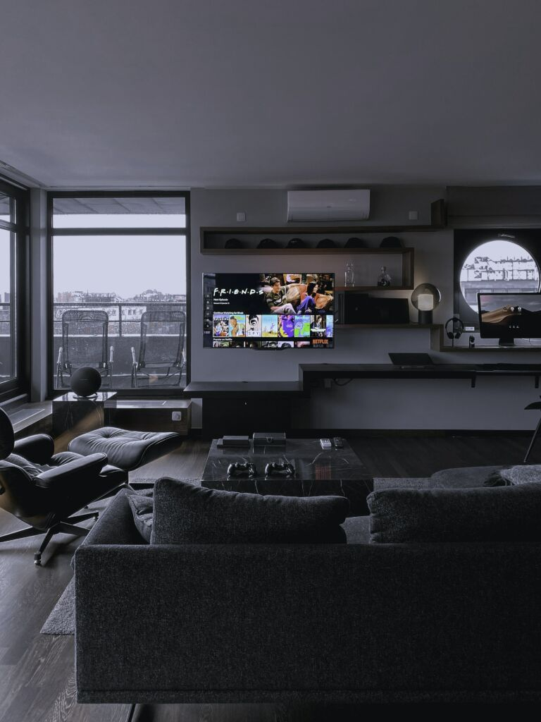 A picture of a mounted TV with hidden speakers which is just one many examples of hiding home theater equipment.